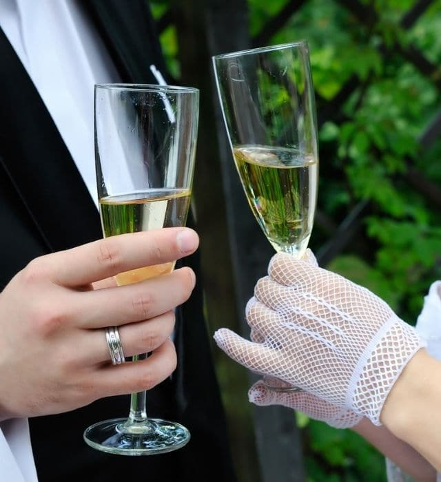 an image of two bottles being held by the groom and bride