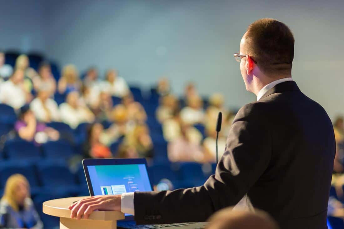 an image of a man talking in front of a crowd