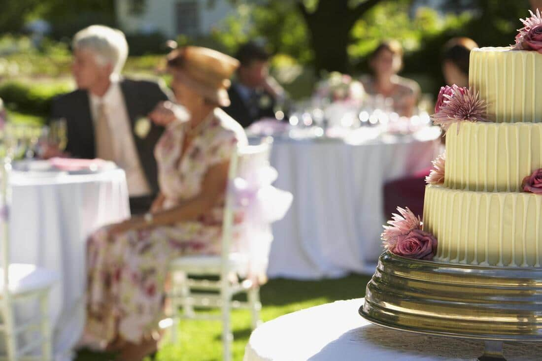 an image of a weeding cake with the guests on the background